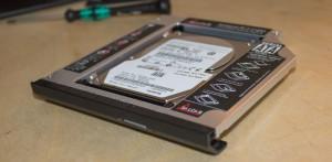 Original verbaute Festplatte im HDD Caddy mit originaler Frontblende.